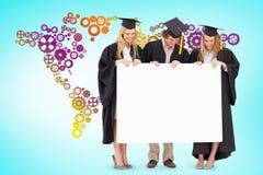 三名微笑的学生的综合图象拿着一个空白的标志的毕业生长袍的 免版税库存图片