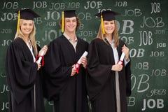 三名微笑的学生的综合图象拿着文凭的毕业生长袍的 库存照片
