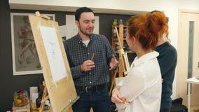 三名快乐的艺术系学生谈论绘在演播室 股票录像