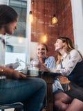 三名愉快的妇女喝咖啡,聊天和说闲话在办公室 免版税库存图片