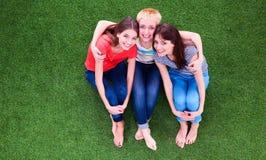三名放松的美丽的挥动的妇女坐绿草 库存图片