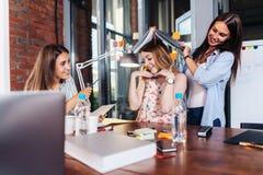 三名滑稽的年轻学生获得乐趣,当坐在书桌为检查做准备在书房时 免版税库存照片