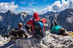 三名登山家坐在Prisojnik山的上面的岩石 免版税图库摄影