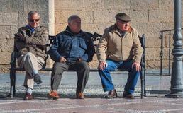三名老人坐长凳 免版税库存图片