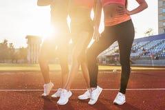 三名运动员适合的妇女的美好的腿体育场的 免版税库存照片