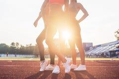 三名运动员适合的妇女的美好的腿在体育场内 免版税库存照片