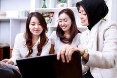 三名年轻女实业家谈论关于他们的工作 库存照片