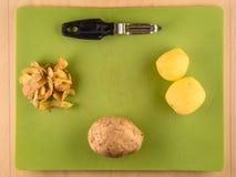 三土豆和皮肤在绿色塑料委员会 图库摄影