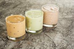 三在一块玻璃的新鲜的自创酸奶用李子、猕猴桃和无花果 在与拷贝空间的具体背景 免版税库存图片