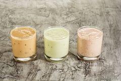 三在一块玻璃的新鲜的自创酸奶用李子、猕猴桃和无花果 在与拷贝空间的具体背景 库存照片