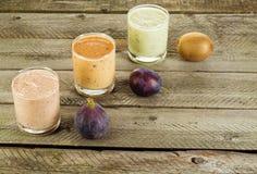 三在一块玻璃的新鲜的自创酸奶用李子、猕猴桃和无花果 在与拷贝空间的具体背景 库存图片