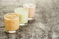 三在一块玻璃的新鲜的自创酸奶用李子、猕猴桃和无花果 在与拷贝空间的具体背景 图库摄影