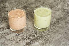 三在一块玻璃的新鲜的自创酸奶用李子、猕猴桃和无花果 在与拷贝空间的具体背景 免版税库存照片