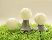 三在不同的支持的高尔夫球,在草的发球区域 免版税库存图片