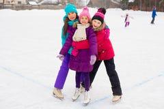 三在冰的有吸引力的溜冰者女孩拥抱 免版税库存图片