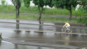 三在夏天在雨中的装备了骑自行车者骑自行车 股票视频