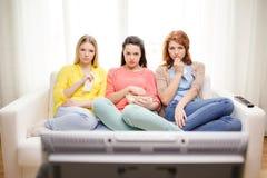 三在家看电视的哀伤的十几岁的女孩 免版税图库摄影