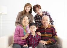 三在沙发的世代亚洲家庭 库存照片