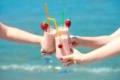 三在经典玻璃杯子的果汁圆滑的人莓果turquois海水背景 三女孩欢呼 免版税图库摄影