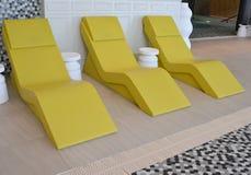 三在水池的黄色躺椅 库存图片