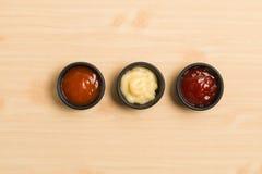 三在黑碗的调味汁在木背景 图库摄影