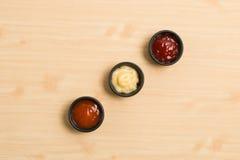 三在黑碗的调味汁在木背景 库存照片