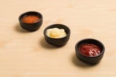 三在黑碗的调味汁在木背景 免版税库存照片