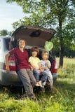 三坐在汽车的后车箱的快乐的孩子 免版税库存图片