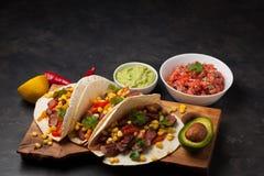 三块墨西哥炸玉米饼用使有大理石花纹的牛肉、黑人安格斯和菜在木板在黑暗的石背景 与sa的墨西哥盘 库存照片