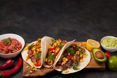 三块墨西哥炸玉米饼用使有大理石花纹的牛肉、黑人安格斯和菜在木板在黑暗的石背景 与sa的墨西哥盘 免版税库存图片