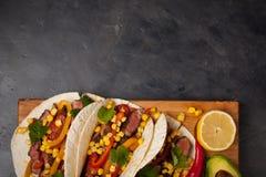 三块墨西哥炸玉米饼用使有大理石花纹的牛肉、黑人安格斯和菜在木板在黑暗的石背景 与sa的墨西哥盘 免版税图库摄影