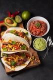 三块墨西哥炸玉米饼用使有大理石花纹的牛肉、黑人安格斯和菜在木板在黑暗的石背景 与sa的墨西哥盘 库存图片