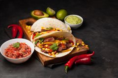 三块墨西哥炸玉米饼用使有大理石花纹的牛肉、黑人安格斯和菜在木板在黑暗的石背景 与sa的墨西哥盘 免版税库存照片