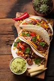 三块墨西哥炸玉米饼用使有大理石花纹的牛肉、黑人安格斯和菜在老土气桌上 与调味汁鳄梨调味酱捣碎的鳄梨酱和婆罗双树的墨西哥盘 库存照片