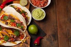 三块墨西哥炸玉米饼用使有大理石花纹的牛肉、黑人安格斯和菜在老土气桌上 与调味汁鳄梨调味酱捣碎的鳄梨酱和婆罗双树的墨西哥盘 免版税库存照片