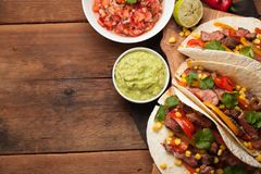 三块墨西哥炸玉米饼用使有大理石花纹的牛肉、黑人安格斯和菜在老土气桌上 与调味汁鳄梨调味酱捣碎的鳄梨酱和婆罗双树的墨西哥盘 库存图片