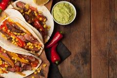 三块墨西哥炸玉米饼用使有大理石花纹的牛肉、黑人安格斯和菜在老土气桌上 与调味汁鳄梨调味酱捣碎的鳄梨酱和婆罗双树的墨西哥盘 免版税库存图片