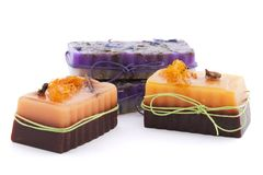 三块巧克力橙色肥皂用丁香、八角茴香属、桂香、丝瓜络和野花在上面在白色背景 库存照片