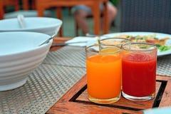 三块玻璃用新近地被紧压的汁液:蕃茄,芒果,桔子在一张老木餐桌上站立 库存照片