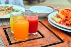 三块玻璃用新近地被紧压的汁液:蕃茄,芒果,桔子在葡萄酒木桌上站立 库存照片