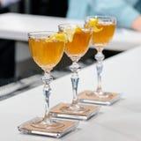三块玻璃线与橙色鸡尾酒的在酒吧柜台, selec 免版税库存照片