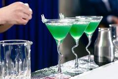 三块玻璃线与绿色鸡尾酒的在酒吧柜台,精选 图库摄影