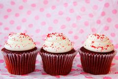 三块红色天鹅绒杯形蛋糕行  免版税库存照片