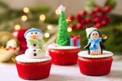三块装饰圣诞节杯形蛋糕有传统背景 免版税库存照片