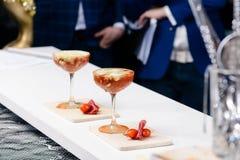 三块马蒂尼鸡尾酒玻璃线与红色鸡尾酒的在酒吧柜台, 图库摄影