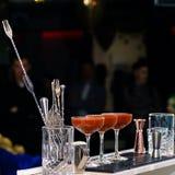 三块马蒂尼鸡尾酒玻璃线与红色鸡尾酒的在酒吧柜台, 库存图片