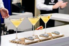 三块马蒂尼鸡尾酒玻璃线与黄色鸡尾酒的在酒吧counte 库存照片