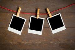 三垂悬在木背景的空白的照片框架 免版税库存照片