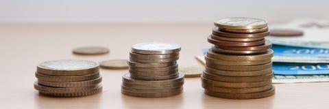 三堆硬币和票据在木桌上说谎 库存图片