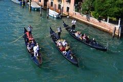三威尼斯,意大利gondoloas美丽的五颜六色的,有意大利建筑学、小船和桥梁的在运河 免版税库存图片